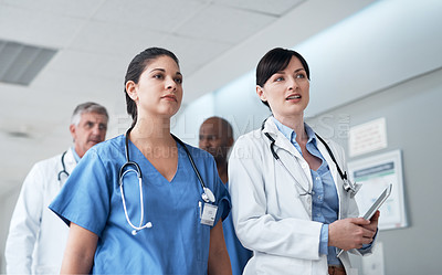 Buy stock photo Cropped shot of a medical team walking through their hospital corridor
