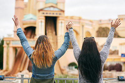 Buy stock photo Rearview shot of two unrecognizable female best friends at an amusement park outside