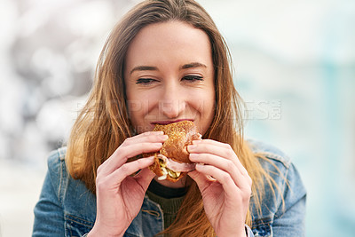 Buy stock photo Portrait of a beautiful young woman eating a sandwich at an amusement park outside