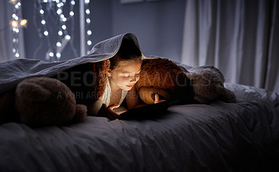Buy stock photo Shot of an adorable little girl using a digital tablet in bed at night