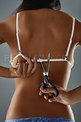 Buy stock photo Studio shot of an unrecognizable woman cutting her bra strap at the back against a gray background