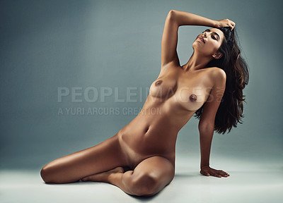 Buy stock photo Studio shot of an attractive young woman posing nude against a grey background
