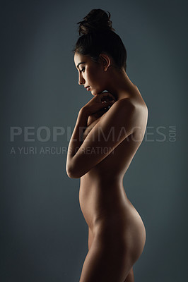 Buy stock photo Studio shot of an attractive young woman posing nude against a black background
