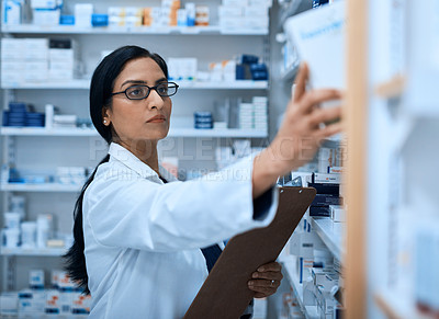 Buy stock photo Shot of a young pharmacist searching the shelves a chemist