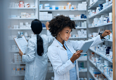 Buy stock photo Shot of a young woman doing inventory in a pharmacy on a digital tablet with her colleague in the background