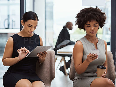 Buy stock photo Shot of two businesswomen using wireless devices while waiting in line for an interview