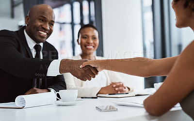 Buy stock photo Shot of businesspeople shaking hands during an interview in an office