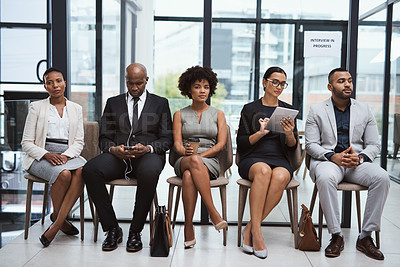 Buy stock photo Shot of a group of businesspeople waiting in line in an office