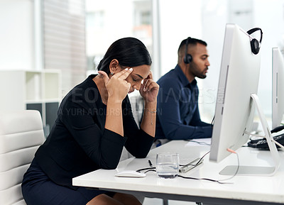 Buy stock photo Shot of a young businesswoman looking stressed out while working in a call centre