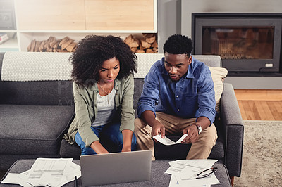 Buy stock photo Shot of a couple sitting with paperwork and their laptop at home