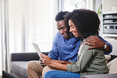 Buy stock photo Cropped shot of a young couple using a digital tablet together at home of a young couple at home