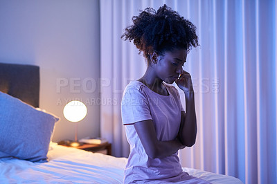 Buy stock photo Cropped shot of a young woman sitting alone in her bedroom