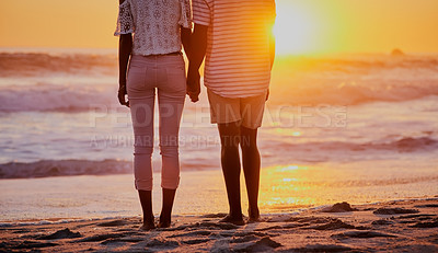 Buy stock photo Cropped shot of an unrecognizable couple at the beach at sunset
