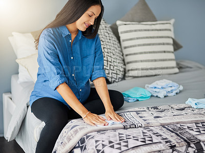 Buy stock photo Shot of a pregnant woman sorting baby clothes at home