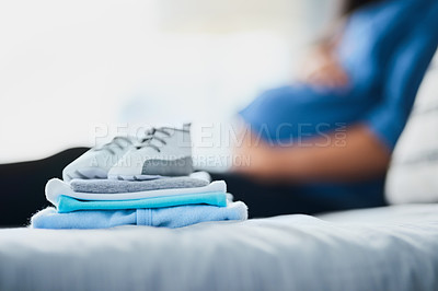 Buy stock photo Closeup shot of baby clothes on a bed with a pregnant woman in the background