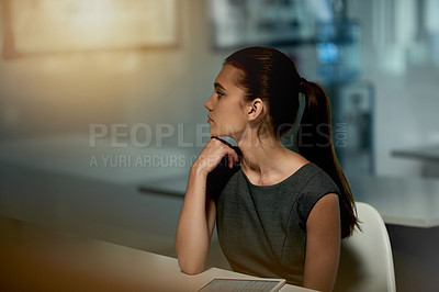 Buy stock photo Shot of a young businesswoman using a digital tablet at night in an office
