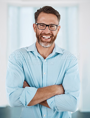 Buy stock photo Cropped portrait of a handsome mature businessman standing with his arms folded in his modern office