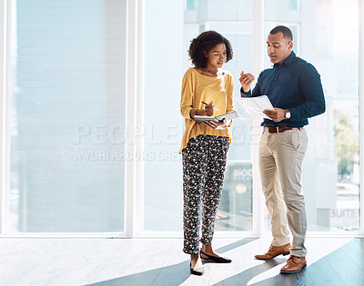 Buy stock photo Full length shot of two young creative colleagues working on some paperwork in their modern office