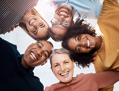 Buy stock photo Low angle portrait of a group of creative businesspeople standing in a huddle in their office