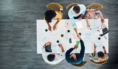 Buy stock photo High angle shot of a group creative businesspeople sitting around a table in the boardroom