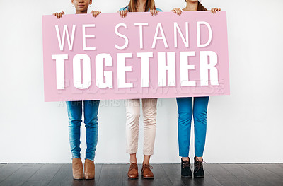 "Buy stock photo Cropped studio shot of a group of young women holding a placard with the words ""we stand together"" on it"