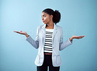 Buy stock photo Studio shot of a young businesswoman gesturing with her hands against a blue background