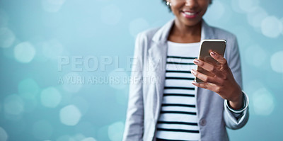 Buy stock photo Cropped studio shot of a young businesswoman using a mobile phone against a blue background