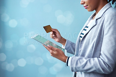 Buy stock photo Cropped studio shot of a businesswoman using a credit card and digital tablet against a blue background