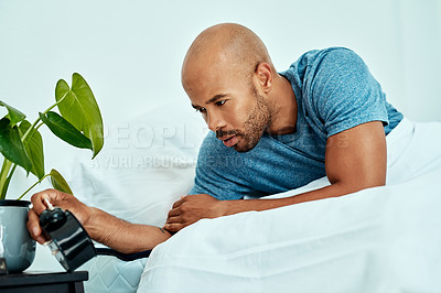 Buy stock photo Cropped shot of a man looking at his alarm clock while lying in bed