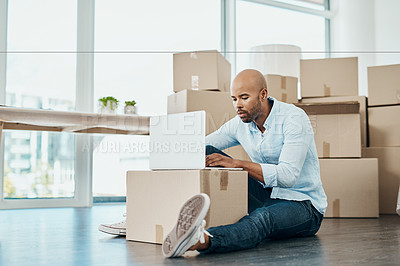 Buy stock photo Shot of a young man using a laptop while moving house