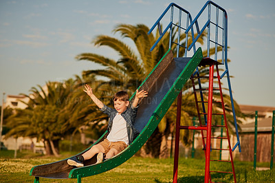 Buy stock photo Shot of an adorable little boy sliding down a slide at a playground outside