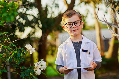 Buy stock photo Cropped shot of an adorable little boy pretending to be a scientist by exploring the plants outside using a tablet