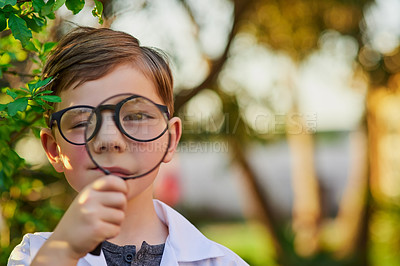Buy stock photo Portrait of an adorable little boy pretending to be a scientist by exploring the plants outside using a magnifying glass
