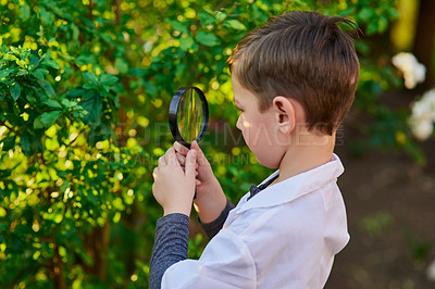 Buy stock photo Cropped shot of an adorable little boy pretending to be a scientist by exploring the plants outside using a magnifying glass