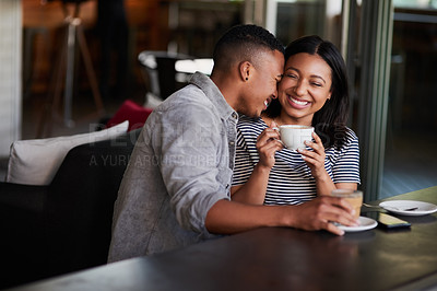 Buy stock photo Shot of an affectionate young couple having coffee on a date in a cafe