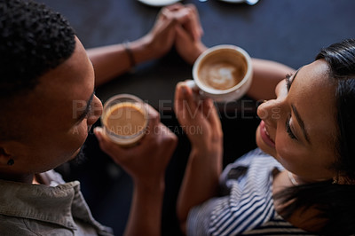 Buy stock photo High angle shot of an affectionate young couple having coffee on a date in a cafe