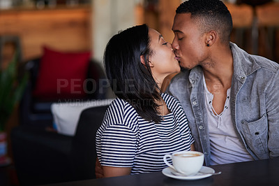 Buy stock photo Shot of a young couple kissing on a date in a cafe