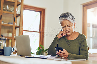 Buy stock photo Shot of a mature woman using a cellphone while going through paperwork at home