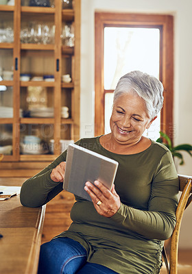 Buy stock photo Shot of a mature woman using a digital tablet at home