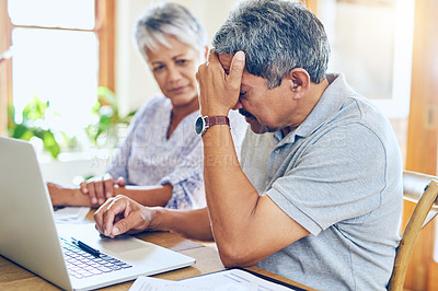 Buy stock photo Shot of a mature couple looking stressed out while managing their paperwork together at home