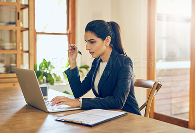 Buy stock photo Shot of a young businesswoman working on a laptop in her home office