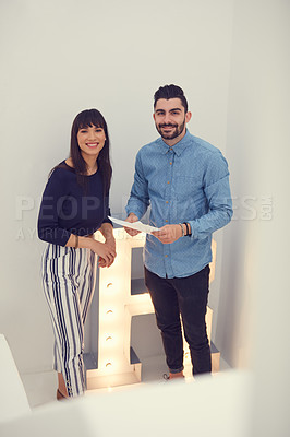 Buy stock photo Portrait of a young businessman and businesswoman going over paperwork in a modern office