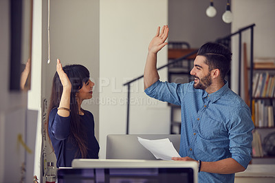Buy stock photo Shot of a young businessman and businesswoman giving each other a high five in a modern office