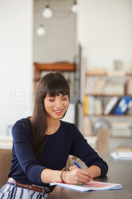 Buy stock photo Shot of a young businesswoman working through paperwork her desk in a modern office