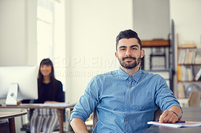 Buy stock photo Portrait of a young businessman working at her desk in a modern office
