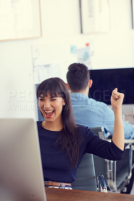 Buy stock photo Shot of a young businesswoman cheering while using a computer at her desk in a modern office