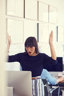 Buy stock photo Shot of a young businesswoman using a computer and looking stressed out at her desk in a modern office