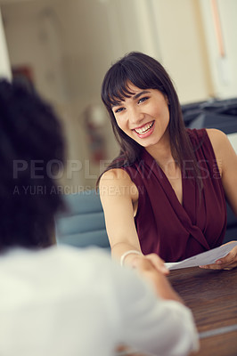 Buy stock photo Cropped shot of two businesswoman shaking hands before an interview at the office