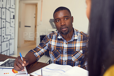 Buy stock photo Shot of a young businessman and businesswoman discussing paperwork in a modern office
