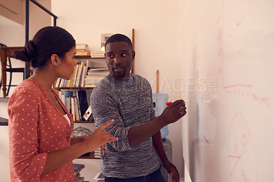 Buy stock photo Shot of a young businessman and businesswoman having a brainstorming session on a wall in a modern office